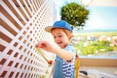 帮助逗人喜爱的愉快的男孩设定在露台的一个格子 库存照片