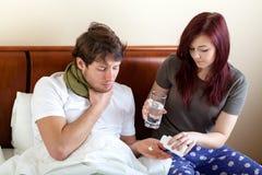 帮助他不适的男朋友的妇女 图库摄影