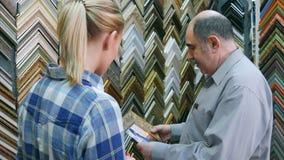 帮助年轻女性顾客的老人工作者拾起一张图片的框架在工作室 库存照片