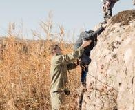 帮助年轻男孩攀岩的侦察员 免版税图库摄影