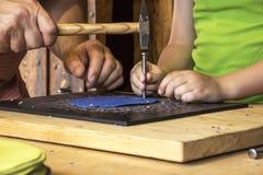 帮助年轻男孩的成人人工作老贸易 库存照片