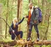 帮助他的女朋友的英俊的有胡子的人得到在树日志 图库摄影