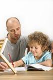 帮助他的有他的家庭作业的父亲儿子 库存图片