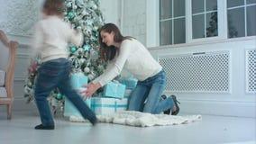 帮助他的母亲的小男孩投入礼物盒在圣诞树下 影视素材