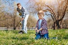 帮助他的父亲的小男孩在庭院里 库存图片