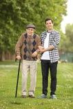 帮助他的祖父的孙子在公园 免版税库存照片