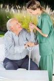 帮助年长人的女性看守者起来 库存照片