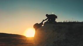 帮手剪影在两登山人之间的 在山顶部的两个远足者,一个人帮助一个人攀登纯粹 股票录像
