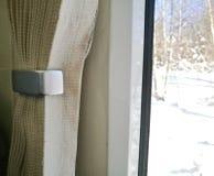 帷幕看明亮的雪场面的开窗口在冬天 库存图片