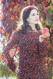 常设秋天女孩画象秋天头花圈的用在胳膊的红色苹果 免版税库存图片