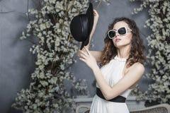 黑帽会议、太阳镜和一件白色礼服的美丽的妇女 图库摄影