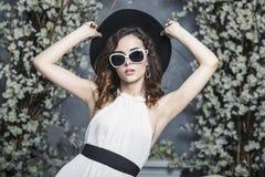 黑帽会议、太阳镜和一件白色礼服的美丽的妇女 库存图片