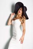 黑帽会议和白色典雅的摆在背景的晚礼服的美丽的白肤金发的妇女 塑造查找 时髦 免版税库存图片