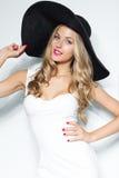 黑帽会议和白色典雅的摆在被隔绝的背景的晚礼服的美丽的白肤金发的妇女 塑造查找 时髦 免版税库存图片
