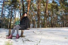 戴黑帽会议的一个年轻美丽的微笑的红色头发欧洲女孩的画象坐长凳在看边的森林里 免版税库存图片