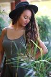 黑帽会议的俏丽的棕褐色的女孩在绿色庭院里  图库摄影