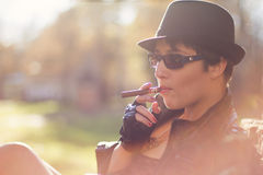 黑帽会议的女孩抽雪茄 免版税库存图片