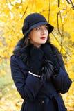 黑帽会议的妇女在秋天树背景  免版税库存照片