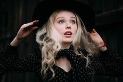 戴黑帽会议的美丽的可爱和时髦的女孩站立摆在城市 裸体构成,最好每日发型和伟大的fashi 免版税库存照片