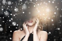黑帽会议的美丽的妇女在城市和雪 免版税库存图片