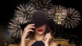 黑帽会议的美丽的妇女在夜烟花 库存图片