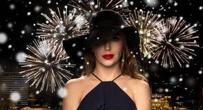 黑帽会议的美丽的妇女在夜烟花 免版税库存照片