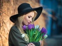 黑帽会议的美丽的白肤金发的女孩享用郁金香花束 免版税库存图片