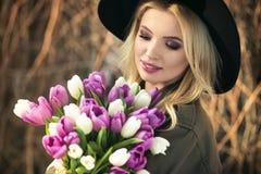 黑帽会议的美丽的白肤金发的女孩享用郁金香花束 免版税图库摄影