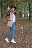 黑帽会议的美丽的逗人喜爱的快乐的女孩有明亮的色的叶子花束的在外套的在秋天公园走 库存图片