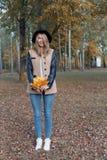 黑帽会议的美丽的逗人喜爱的快乐的女孩有明亮的色的叶子花束的在外套的在秋天公园走 免版税库存照片