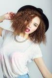 黑帽会议的年轻美丽的愉快的妇女,明亮的构成,卷发,时尚白色背景的摄影演播室 免版税库存照片
