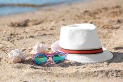 帽子、太阳镜和壳在沙子在海附近 库存照片