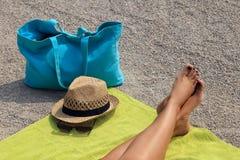 帽子、海滩袋子和玻璃在地毯 免版税库存图片