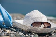 帽子、袋子和玻璃在海滩 图库摄影