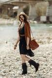 帽子、边缘雨披和起动的走时髦的行家的妇女  库存照片