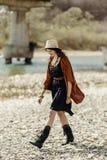 帽子、边缘雨披和起动的走时髦的行家的妇女  库存图片