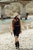帽子、边缘雨披和起动的走时髦的行家的妇女  免版税库存图片
