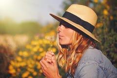 帽子吹的蒲公英的白肤金发的妇女在夏天 免版税库存图片