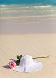 帽子和在沙子的一朵玫瑰。 免版税库存照片
