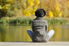帽子和外套的女孩坐船坞 秋天,晴朗 backarrow 免版税库存照片