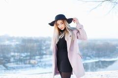 帽子和外套的年轻美丽的女孩在一个冬天的背景 免版税库存照片