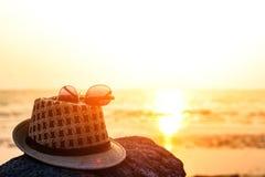 帽子和太阳镜在岩石在海滩和日落附近 库存照片