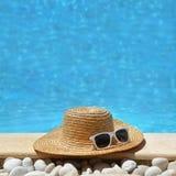帽子和太阳镜由游泳池边 库存图片