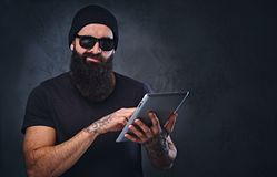 帽子和太阳镜的一个人拿着片剂个人计算机 库存图片