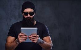 帽子和太阳镜的一个人拿着片剂个人计算机 免版税图库摄影