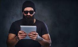 帽子和太阳镜的一个人拿着片剂个人计算机 免版税库存图片