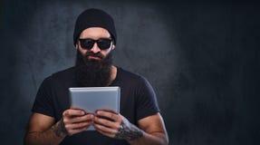 帽子和太阳镜的一个人拿着片剂个人计算机 免版税库存照片