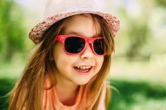 戴帽子和太阳镜的小逗人喜爱的女孩户外 免版税库存照片