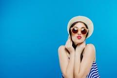 帽子和太阳镜的快乐的美丽的女孩 微笑广泛,看和指向在旁边 夏天成套装备 腰部 免版税库存照片