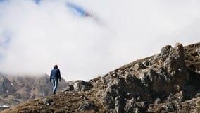 帽子和太阳镜的有胡子的年轻男性摄影师和一台照相机在他的脖子上攀登小山反对 影视素材